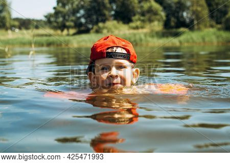 Little Smiling Child In A Red Cap Floating In The Water, Outdoors. Portrait Of A Cute Kid In Life-sa