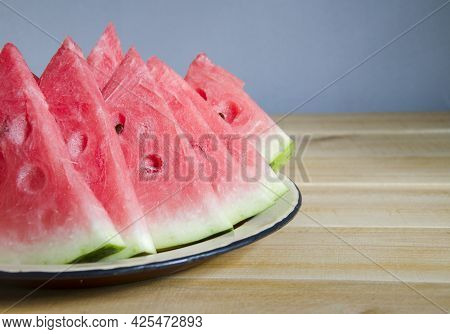 Sliced, Ripe Watermelon On A Tray. Sweet Berries On A Wooden Table. Summer Fruit Is Cut Into Slices.