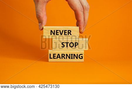 Never Stop Learning Symbol. Wooden Blocks With Concept Words Never Stop Learning. Beautiful Orange B