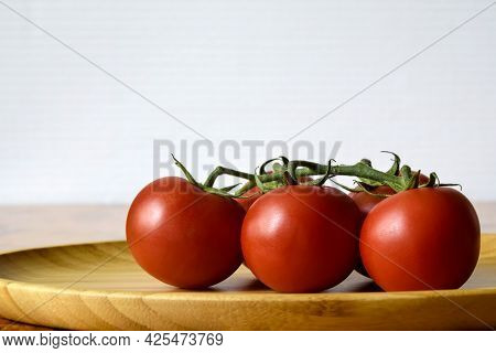 Ripe Fresh Tomato In Wooden Plate On Kitchen Table. Tasty Red Heirloom Tomatoes. Close-up. Copy Spac