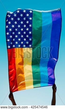 someone waves a rainbow US flag on the blue sky