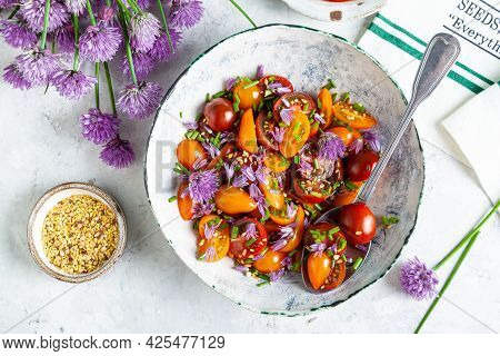 Tomato Salad With Chives Flowers In A White Bowl On A White Background.
