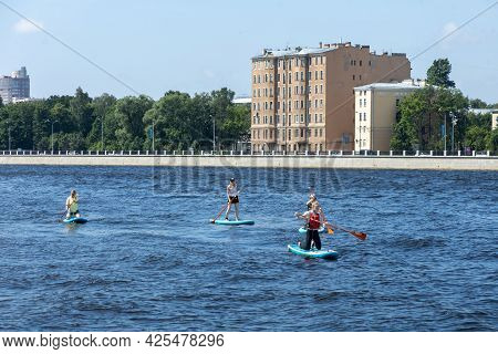 Saint-petersburg, Russia, 26.06.2021. A Group Of People Swims Along The Neva River On Surfboards.