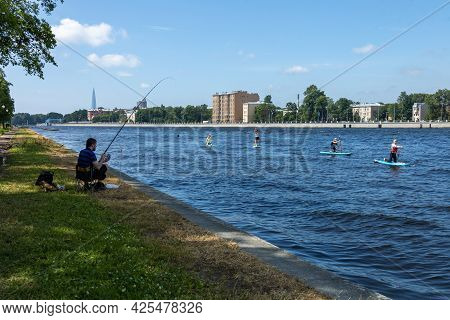 Saint-petersburg, Russia, 26.06.2021. A Fisherman Is Fishing In The Neva River Against The Backgroun