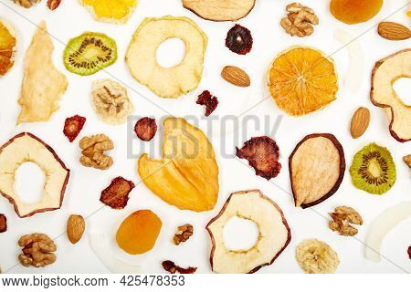 Close Up Of Dried Strawberry, Almonds, Dried Apricot, Raisins, Walnuts, Dried Apples And Kiwi On Whi