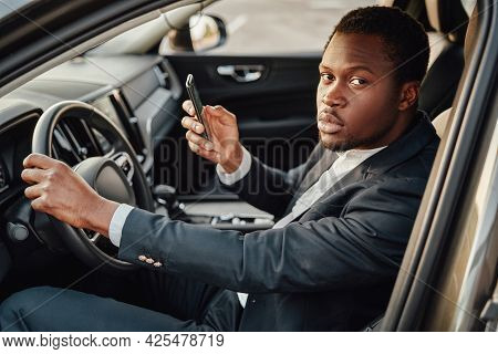 African Businessperson Sitting Inside Car With Smartphone