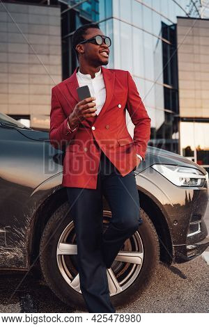 Cheerful African Businessperson With Phone And Car Outside