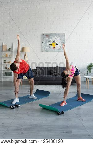 Fit Young Couple In Sportswear Doing Exercise On Fitness Mats At Home