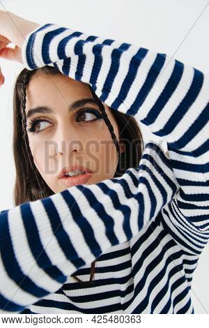 Trendy Armenian Woman In Striped Pullover Looking Away Isolated On White