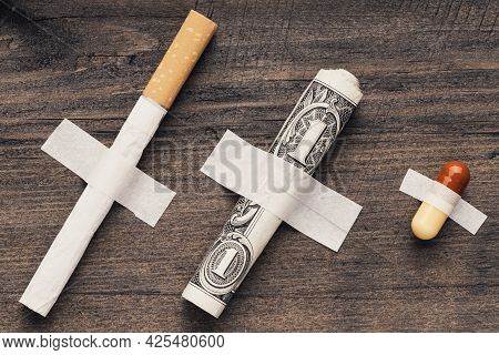 A Dollar Cigarette And A Medical Pill Are Fixed On An Adhesive Tape Against The Wall. Take In Sequen