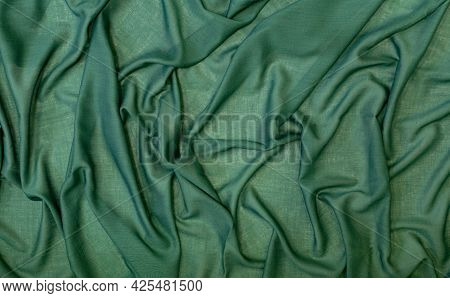 Abstract Background From A Green Fabric Draped With Soft Folds, Copy Space.