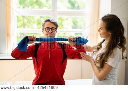 Elderly Man Stretching Rehab Physio Band With Physiotherapist