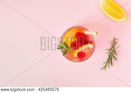 Lemon Water Or Lemonade With Raspberry And Rosemary On A Pink Background, Top View. Aromatic Cool Co