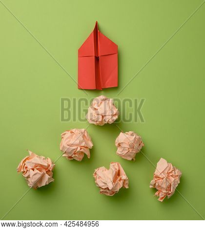 Red Paper Airplane And Crumpled Paper Balls On A Green Background, Top View. The Concept Of Finding
