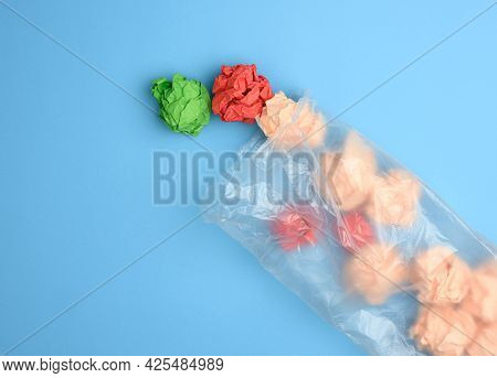 Transparent Plastic Bag With Crumpled Sheets Of Paper On Blue Background, Top View