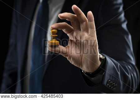Business Planning Strategy And Concept. A Businessman In A Dark Suit Holds A White Chess Pawn On A S