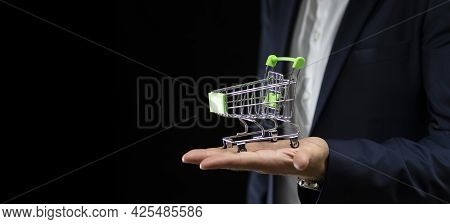 Business Man Holding Shopping Cart On Black Background With Place For Text
