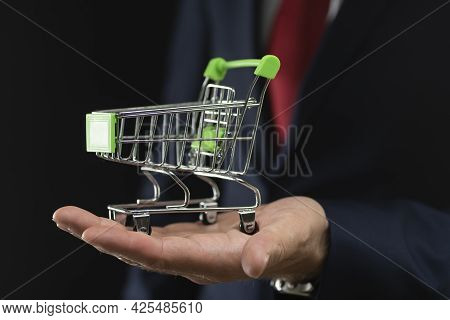 Business Man Holding A Shopping Cart On A Black Background