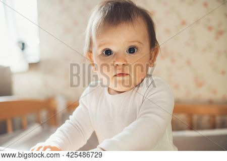 Close Up Photo Of A Small Baby Looking Enthusiastic At The Camera