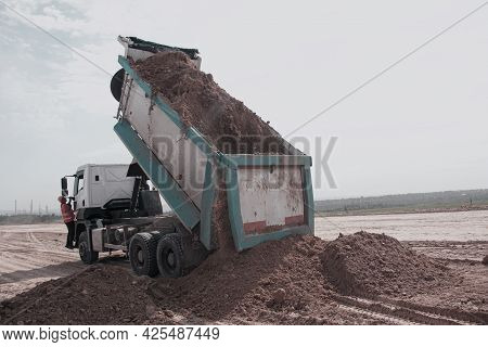 Dnepropetrovsk, Ukraine - 06.26.2021: Dump Truck Unloads Clay Soil For The Construction Of A New Hig