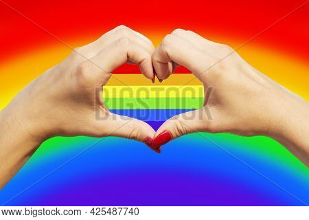 Gay Pride Concept. Womans Hands Making Heart Sign With Gay Pride Lgbt Rainbow Flag.