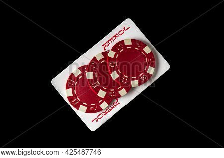 Joker Card And Red Chips In The Black Background. Winning Combination At A Poker Club Or Casino. Fre