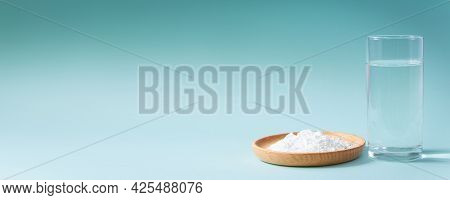 Collagen Powder And Glass Of Pure Water On Blue Background. Natural Bio Supplement For Skin, Bone An