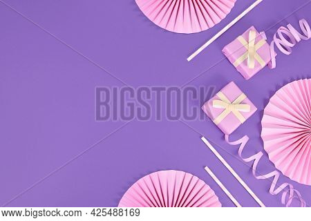 Violet Party Flat Lay With Pink Gift Boxes, Paper Streamers, Drinking Straws And Paper Rosettes With