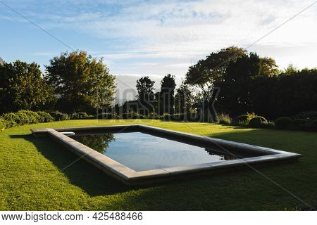 General view of tranquil swimming pool in stunning sunny countryside. outdoor retreat and holiday concept.