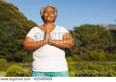 Senior african american woman with eyes closed practicing yoga in stunning countryside. retirement and active senior lifestyle concept.