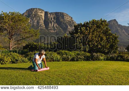 Senior african american woman putting yoga mat on grass in stunning countryside. retirement and active senior lifestyle concept.