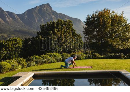 Senior african american woman on yoga mat on grass by outdoor pool in stunning countryside. retirement and active senior lifestyle concept.
