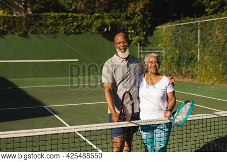 Portrait of smiling senior african american couple with tennis rackets on tennis court. retirement and active senior lifestyle concept.