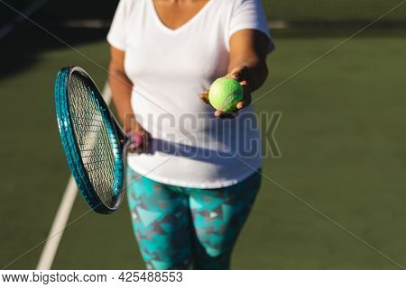 Midsection of senior african american woman holding tennis racket and ball on tennis court. retirement and active senior lifestyle concept.
