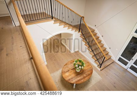 General view of house interior with table and vase with flowers in spacious hallway and staircase. modern interiors and house decoration concept.