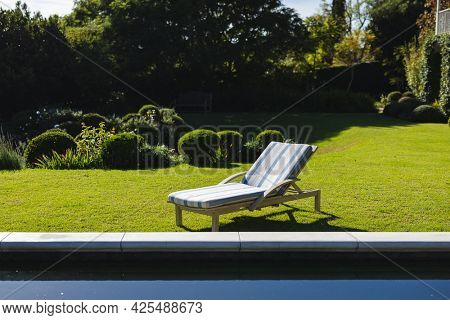 General view of tranquil swimming pool and deckchair with stunning mountains countryside. outdoor retreat and holiday concept.