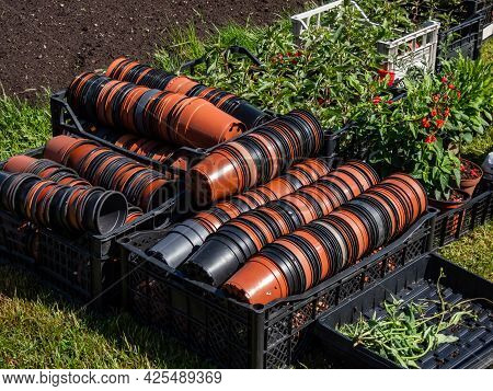 Black Plastic Boxes Full With Empty Brown And Black Plastic Pots Stacked Together For Plants With Bo