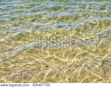 Texture Of Crystal Clear Light Blue Transparent Water With Fine White Sand Base With Bright Reflecti
