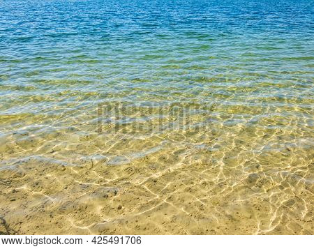 Texture Of Crystal Clear Light Blue, Green And Turquoise Transparent Water With Fine White Sand Base