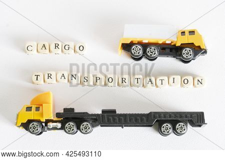 Cargo Transportation Lettering Next To Two Toy Trucks. The Concept Of Transportation And Delivery Of