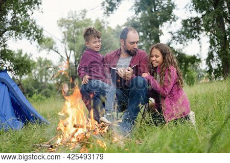 Father, Daugther And Son Sit And Read Book At Campfire In Forest