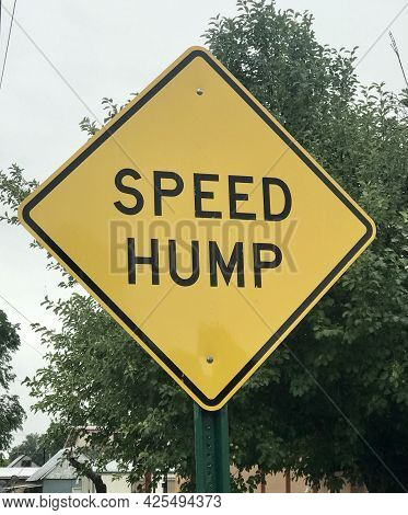 Yellow Speed Bump Sigh On City Street, Humorous Sign