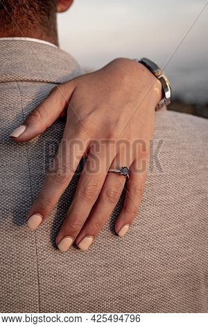 Beautiful Proposal Ring On A Hand Over A Shoulder With The Beach In The Background