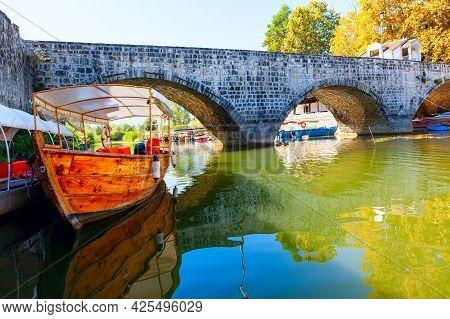 Medieval Arch Bridge In Virpazar Montenegro . Water Canal Of Skadar Lake . Travel Cruise Boats