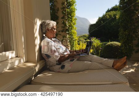 Senior african american woman using laptop on shaded terrace in sunny garden. retreat, retirement and happy senior lifestyle concept.