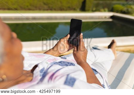 Senior african american woman using smartphone in deckchair by swimming pool in sunny garden. retreat, retirement and happy senior lifestyle concept.