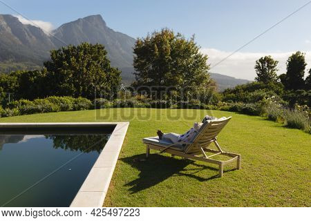 Senior african american woman relaxing in deckchair by swimming pool in sunny garden. retreat, retirement and happy senior lifestyle concept.