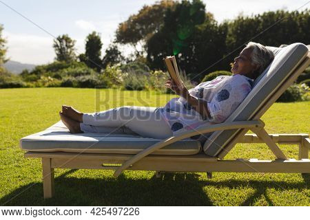 Senior african american woman reading book in deckchair in sunny garden. retreat, retirement and happy senior lifestyle concept.