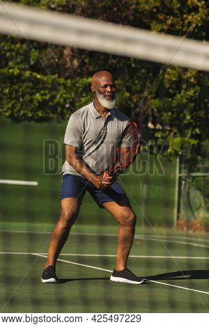 Senior african american man playing tennis on tennis court. retirement and active senior lifestyle concept.