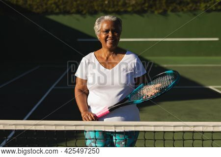 Portrait of smiling senior african american woman holding tennis racket on tennis court. retirement and active senior lifestyle concept.